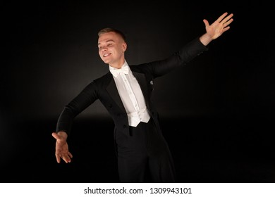 Elegant toung man dancing in studio with expression, posing with smile on black background