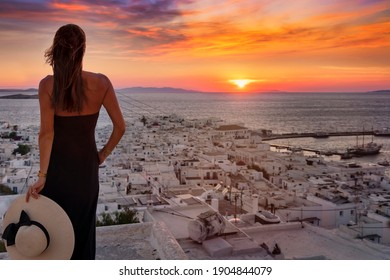 A elegant tourist woman in a black dress enjoys the view of the city of Mykonos island during summer sunset time, Cyclades, Greece