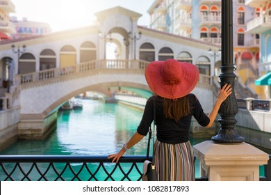 Elegant travel woman enjoys the view to the Qanat Quartier on the Pearl in Doha, Qatar
