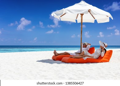 Elegant traveler couple relaxes on a tropical beach in the shade of an umbrella during their summer vacation