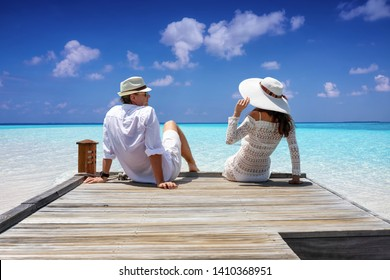 A elegant traveler couple in white linen clothes sitting on a wooden jetty and enjoying their tropical holiday