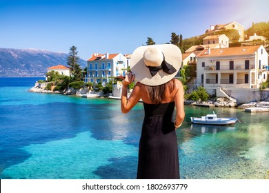A elegant traveler woman with hat looks at the idyllic village of Fiscardo on the island of Kefalonia, Greece, during summer vacation time