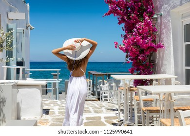 Elegant traveller woman in white dress stands in a typical whitewashed alley on a Greek island in the cyclades, Paros, and enjos the summer