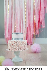 Elegant two-tier birthday or wedding cake with ruffled fondant bottom, decorated with grey satin ribbon. Pastel pompoms on the wooden floor, fabric streamers in the background.