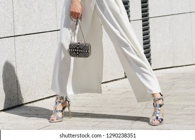 Elegant unrecognizable woman presenting fashionable urban outfit. High heels and trousers culottes.