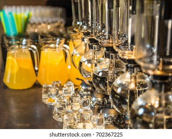 Elegant vacuum glass siphons and blurry orange drinks with slices of orange fruit inside big glass bowls in background. Drinks served on table ready for holiday celebration. Horizontal color photo.