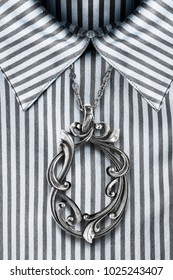 54fdc8f31ee2ac Elegant vintage silver pendant hanging over striped satin blouse closeup