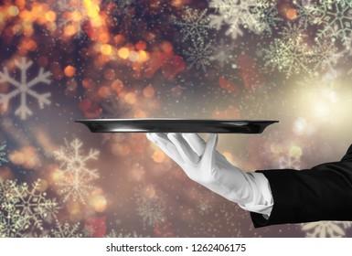 Elegant waiter hand in white glove holding an empty plate