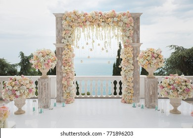 Elegant wedding arch with fresh flowers, vases on background of ocean and blue sky.
