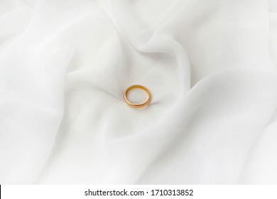 Elegant wedding concept. Golden bridal ring on white silk background. Feminine still life composition. Minimalist style. Top view, copyspace.