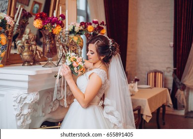 Elegant wedding dress. Gorgeous bride. The bride in a luxurious apartment.