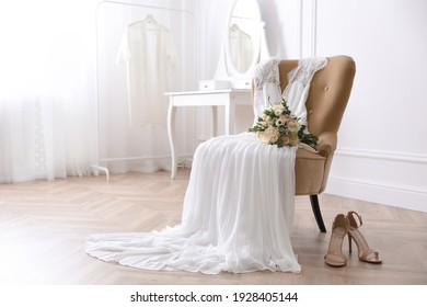 Elegant wedding dress, shoes and bouquet in room - Shutterstock ID 1928405144
