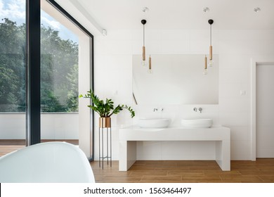 Elegant white bathroom interior with big window, wooden floor and two washbasins