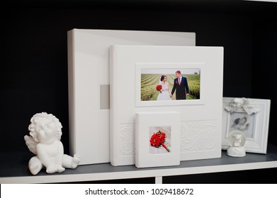 Elegant white or beige photobook, photoalbum and a flash drive case on black background.