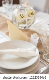 Elegant white and beige wedding table set with lace style sitting cards and floating candle glass bowls