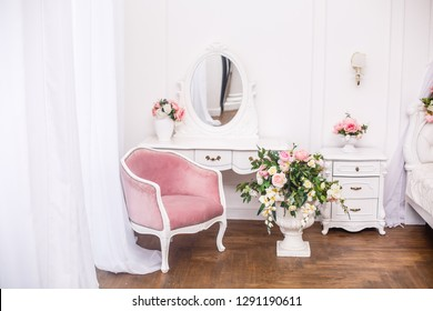Elegant white dressing table in light luxury interior. Boudoir room with pink soft armchair