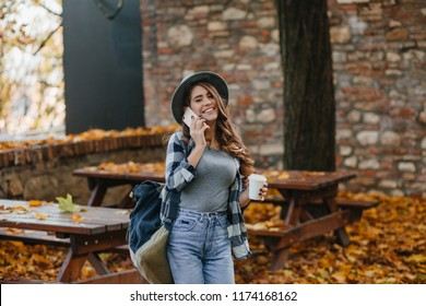 Elegant white girl in trendy denim pants posing in autumn day, walking in park. Outdoor portrait of cute lady in gray hat enjoying warm september morning.