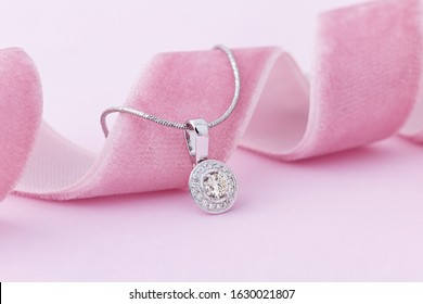 Elegant white gold necklace with diamonds on pastel pink background. Small silver charm necklace with gemstones for romantic occasion