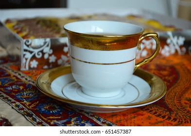 Elegant white and golden cup of tea on Middle Eastern Persian tablecloth