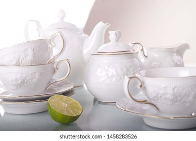 Elegant white porcelain tea set with cups and saucers. Luxury design with porcelain roses. Service arrangement with lemon on a table.