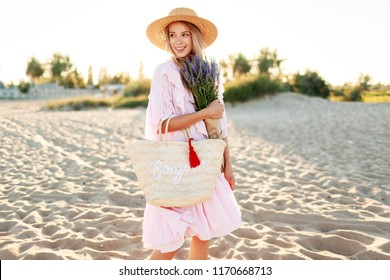 Elegant white woman  with flowers in hands walking on sunny beach . Warm sunset colors. Straw hat.   Pink dress. Holidays and vacation mood.