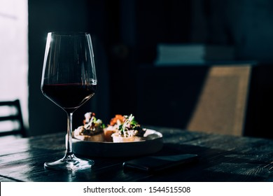 Elegant wine background. Glass with red wine on wooden table with copy space