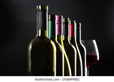 elegant wine bottles and a glass of red wine stand in one row against a dark glossy background.