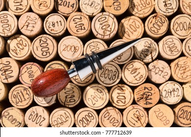 Elegant wine stopper made of wood and metal lies on a background of many different vintage corks