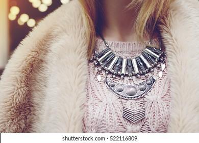 Elegant winter outfit. Close up of massive necklace. Boho style. Fashionable girl on the street. Female fashion. City lifestyle. Toned