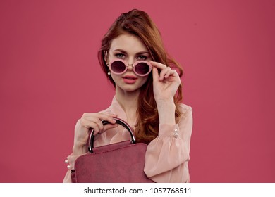elegant woman with a bag and pink glasses