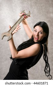 The elegant woman in a black dress with a spanner in hands.