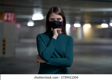 Elegant woman in a black mask in an underground parking lot, protection against virus and infections during an epidemic.