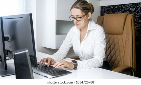 Elegant woman in blouse working on computer at office