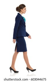 Elegant woman in blue suit, skirt and high heels walking. Side view. Full length studio shot isolated on white.