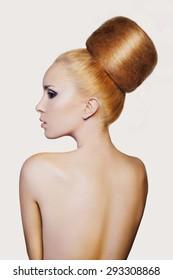 elegant woman with creative hair style. Fashion woman model with creative huge bun hairstyle with big chignon. Beautiful shiny volume hair