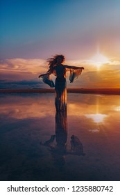 Elegant woman dancing on water. Sunset and silhouette