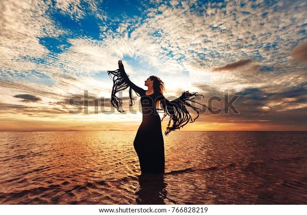 Elegante Frau tanzt auf dem Wasser. Sonnenuntergang und Silhouette