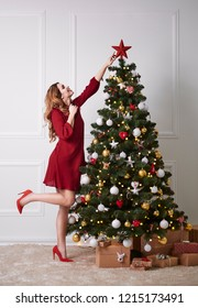 Elegant woman decorating the christmas tree
