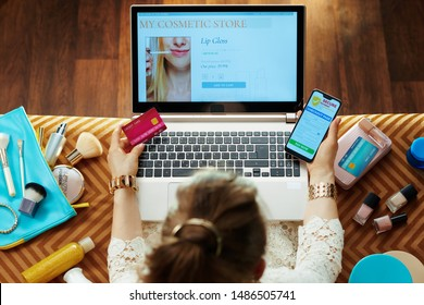 Elegant woman in dress with credit card buying cosmetics while shop online on a laptop and making secure online payments on e-commerce website on smartphone while sitting on couch in the living room.