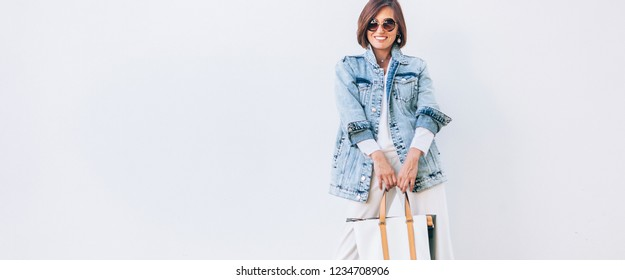 Elegant woman dressed in oversize denim jacket and wide white trousers