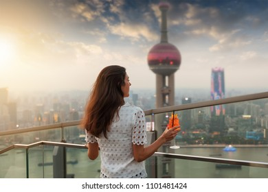 Elegant woman with a drink in her hand enjoys the sunset over the skyline of Shanghai, China