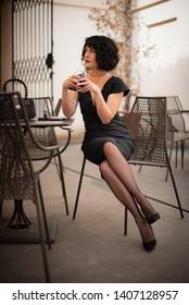 Elegant woman drinking wine and smoking in small Italian bar