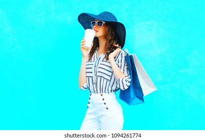 Elegant  woman is drinks coffee from cup wearing a shopping bags, straw hat, white pants over colorful blue background posing in the city