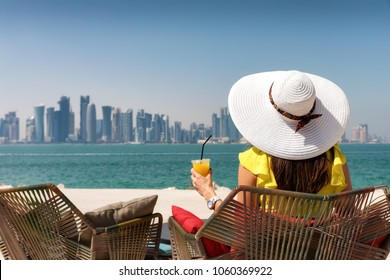 Elegant woman enjoys the view to the skyline of Doha, Qatar, with a refreshing drink in her hand