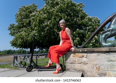 Elegant woman with e-scooter in the park