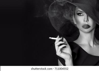 Elegant woman, femme fatale in black hat with cigarette in hand. On black background