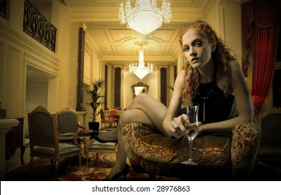 elegant woman with a glass of wine in a luxury interior