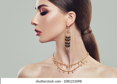 Elegant Woman with Gold Jewelry Earrings and Chain, Close up Portrait