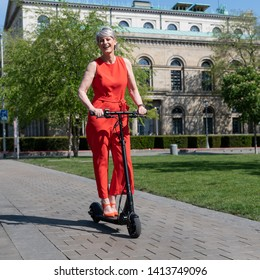 Elegant woman is having fun with e-scooter