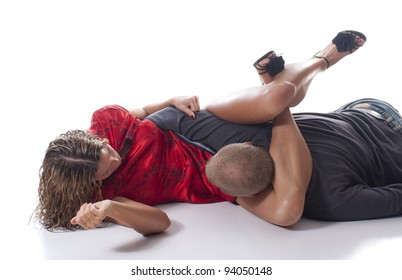 Elegant woman in high heels overpowering an attacker using a triangle choke